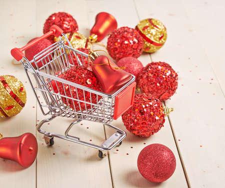 Christmas shopping background compostion of a multiple decoration balls and tiny shopping cart over the wooden surface