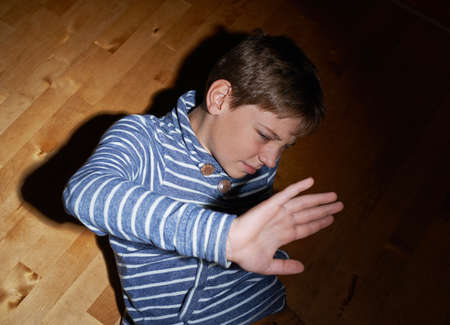 scared boy: Child abuse composition of a frightened young boy sitting on the wooden floor in a light of a flashlight circle Stock Photo