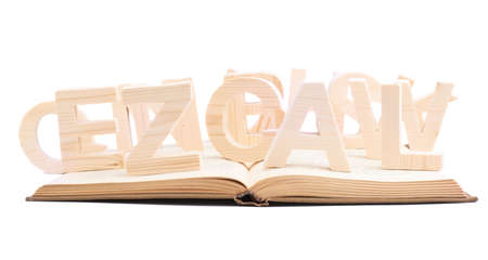 books on a wooden surface: Multiple wooden letters over the opened books surface, composition isolated over the white background