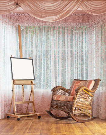 Copyspace empty picture frame on the wooden easel and next to wicker rocking chair, composition against the windows curtains background photo