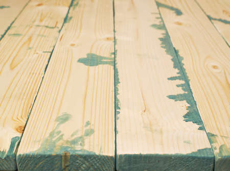 multiple stains: Surface covered with multiple pine wood boards with the paint stains and leaks in the gaps, as an abstract background composition with a shallow depth of field