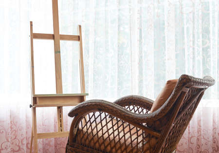 Wicker rocking chair and wooden easel composition against the windows curtains background photo