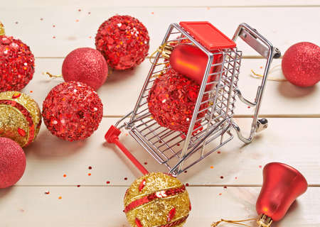 compostion: Christmas shopping background compostion of a multiple decoration balls and tiny shopping cart over the wooden surface