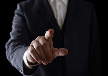 ビジネス スーツ、リラックスの劇的な光の組成の白人男のポインティング指のクローズ アップ撮影 写真素材