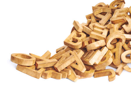 Pile of wooden block letters isolated over the white background as a typography background composition photo