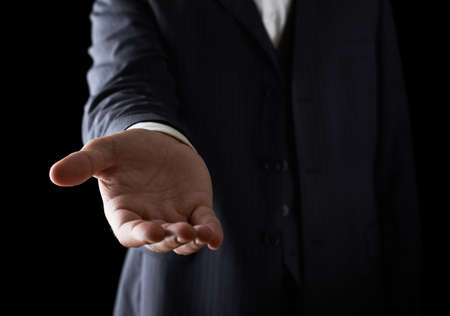 Het geven van een helpende hand, met de vraag of het aanbieden van hulp close-up shot van een blanke man in een pak, low-key dramatische licht samenstelling Stockfoto
