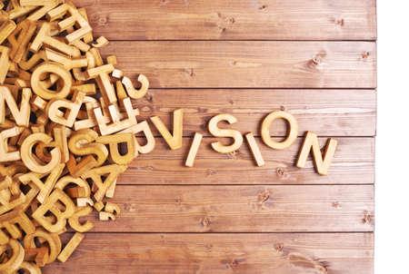 vision futuro: Visi�n Palabra hecha con letras de madera en bloque junto a un mont�n de otras cartas sobre la composici�n de la superficie tabla de madera