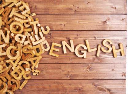aprendizaje: Palabra Inglés hecha con letras de madera en bloque junto a un montón de otras cartas sobre la composición de la superficie tabla de madera Foto de archivo