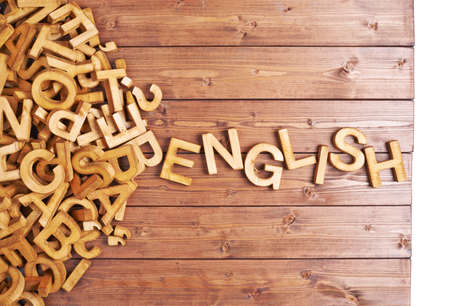 'english: Word english made with block wooden letters next to a pile of other letters over the wooden board surface composition