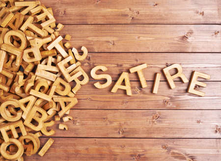 satire: Word satire made with block wooden letters next to a pile of other letters over the wooden board surface composition