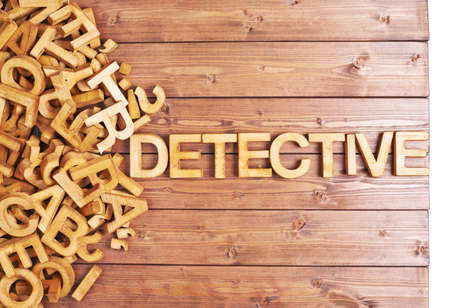 jumbled: Word detective made with block wooden letters next to a pile of other letters over the wooden board surface composition