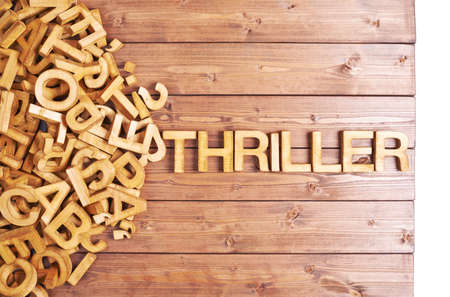 jumbled: Word thriller made with block wooden letters next to a pile of other letters over the wooden board surface composition