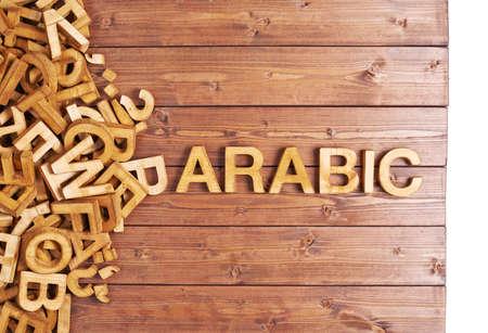 arabische letters: Het woord Arabisch gemaakt met blok houten letters naast een stapel van andere brieven over het oppervlak houten plank samenstelling