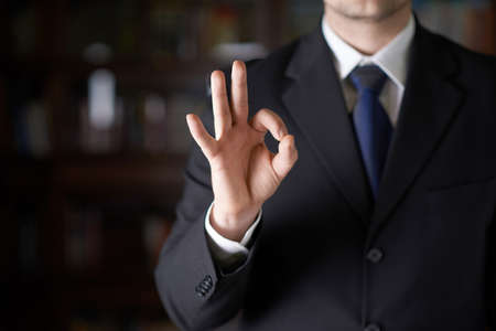 ok hand: Close-up fragment of a man in a business suit showing an ok sign gesture, shallow depth of field composition