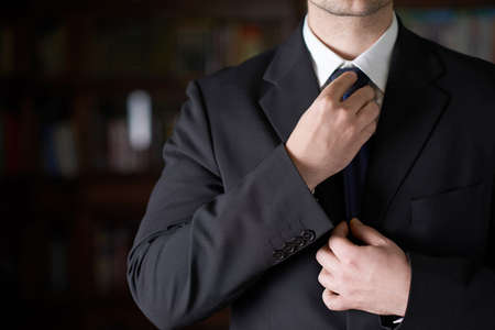 Close-up fragment of a man in a business suit correcting his tie, shallow depth of field composition