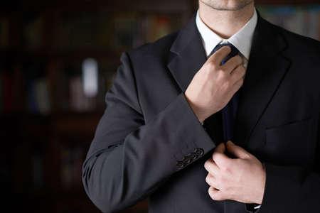corbata negra: Fragmento del primer plano de un hombre en un traje de negocios corregir la corbata, profundidad de campo composici�n Foto de archivo