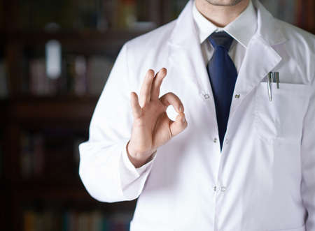 coat and tie: Close-up fragment of a man in a white doctors coat showing an ok sign gesture, shallow depth of field composition Stock Photo