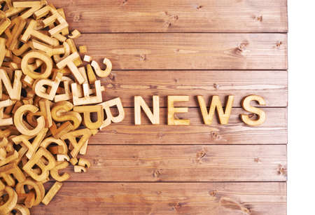 Word news made with block wooden letters next to a pile of other letters over the wooden board surface composition photo