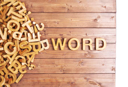 Word word made with block wooden letters next to a pile of other letters over the wooden board surface composition photo