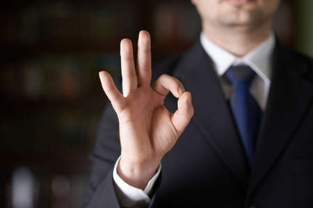 Close-up fragment of a man in a business suit showing an ok sign gesture, shallow depth of field composition