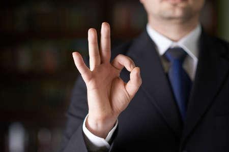 Close-up fragment van een man in een pak met een OK-gebaar, ondiepe scherptediepte samenstelling Stockfoto