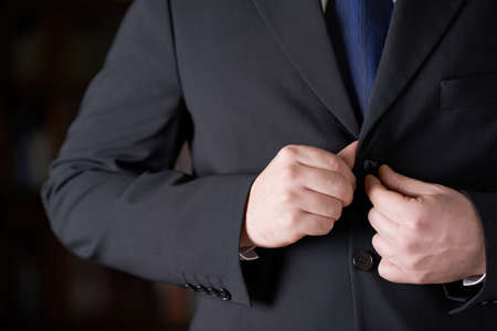 business suit: Close-up fragment of a man in a business suit unbottoning his jacket, shallow depth of field composition