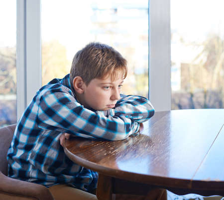 Droevige 12 jaar oude kinderen jongen zitten op het houten bureau, samenstelling tegen het raam