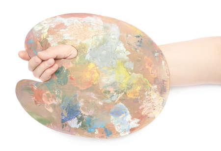 Male hand holding a wooden palette covered with paint, composition isolated over the white background photo