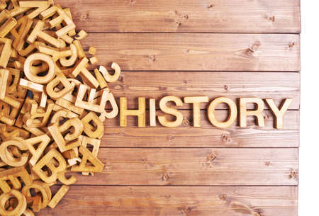 Word history made with block wooden letters next to a pile of other letters over the wooden board surface composition