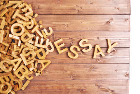 essay: Word essay made with block wooden letters next to a pile of other letters over the wooden board surface composition