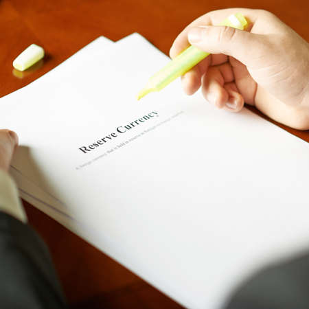 article of clothing: Reserve currency definition as a shallow depth of field close-up composition of a man in a business suit working with the text