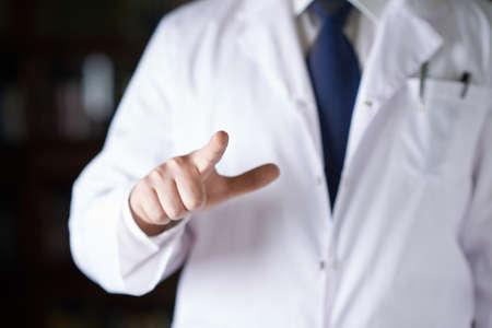 lab coat: Fragmento de primer plano de un hombre en un abrigo blanco m�dicos celebraci�n de un dedo apuntando frente a �l, la profundidad de campo de la composici�n Foto de archivo