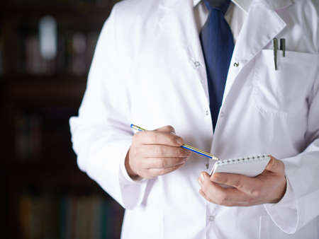 Close-up fragment of a man in a white doctors coat writing down something in a notebook with a pencil, shallow depth of field composition