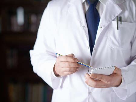 lab coat: Close-up fragmento de un hombre en un abrigo blanco m�dicos escribiendo algo en un cuaderno con un l�piz, profundidad de campo composici�n Foto de archivo