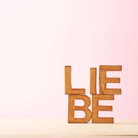 Liebe: Word Liebe meaning Love in German language as a composition of wooden block letters against the pink background