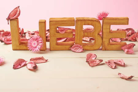 in liebe: Word Liebe meaning Love in German language as a composition of wooden block letters covered with the dried flower potpourri leaves against the pink background