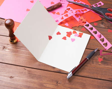 Making valentine card and confetti composition over the wooden surface as a copyspace card template Stock Photo