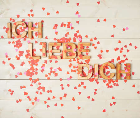 Liebe: Ich Liebe Dich meaning I Love You in German written with the block letters covered with red heart shaped confetti over the wooden background