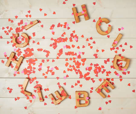in liebe: Ich Liebe Dich meaning I Love You in German written with the block letters covered with red heart shaped confetti over the wooden background
