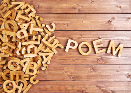 poem: Word poem made with block wooden letters next to a pile of other letters over the wooden board surface composition