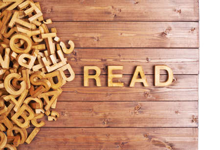 Word read made with block wooden letters next to a pile of other letters over the wooden board surface composition photo
