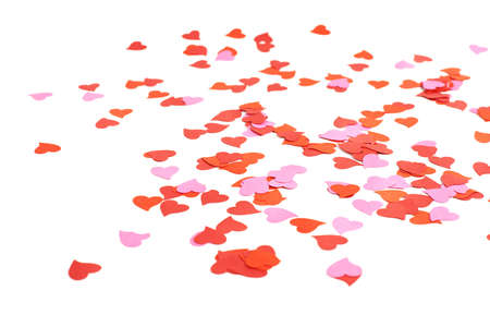 confetti: White surface covered with multiple red and pink heart shaped paper confetti as a romantic background composition