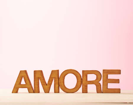 amore: Word Amore meaning Love in Italian language as a composition of wooden block letters against the pink background