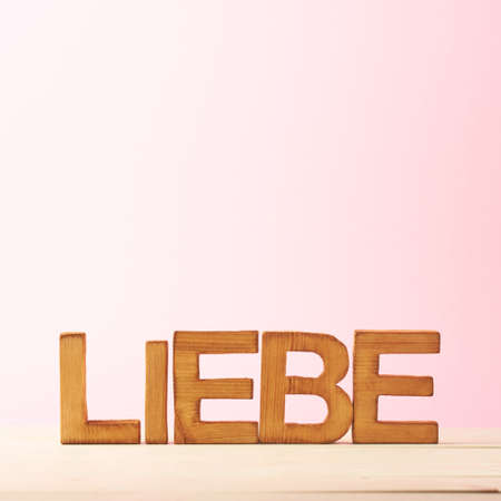 in liebe: Word Liebe meaning Love in German language as a composition of wooden block letters against the pink background