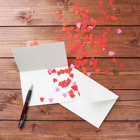 Empty copyspace valentine card or love letter composition over the wooden boards covered surface
