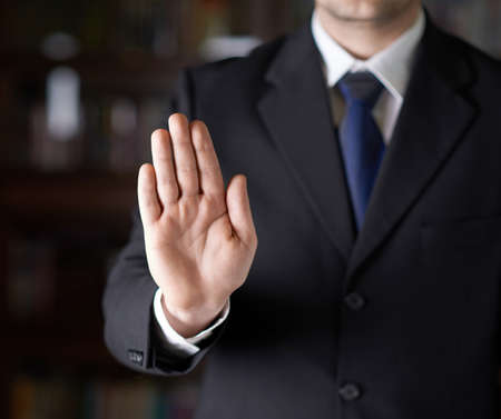 Close-up fragment of a man in a business suit showing an open palm stop sign gesture, shallow depth of field composition photo