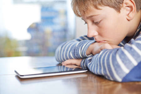 blonde boy: Sad 12 years old children boy sitting at the wooden desk while looking at the tablet pad device