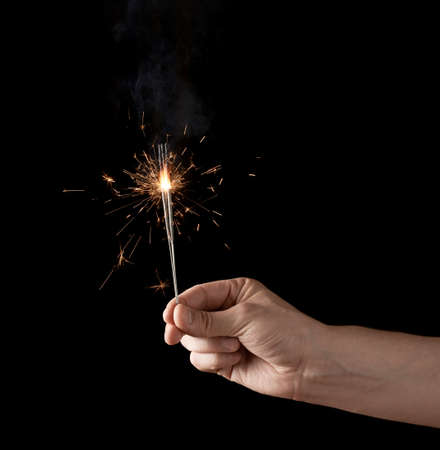 Holding a burning sparkler, low-key composition isolated over the black background photo