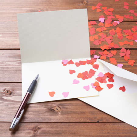 love notes: Empty copyspace valentine card or love letter composition over the wooden boards covered surface