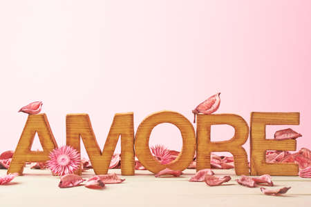 amore: Word Amore meaning Love in Italian language as a composition of wooden block letters covered with the dried flower potpourri leaves against the pink background